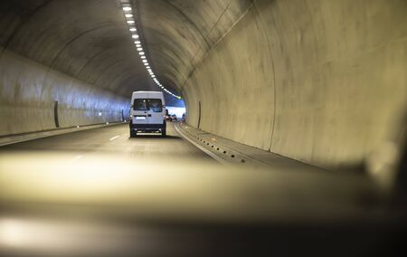 Bus traveling in highway tunnel. Tunnel lights.