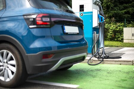 Electric car on gas station. Blue car and electric plug for charging. Ecology green fuels concept.