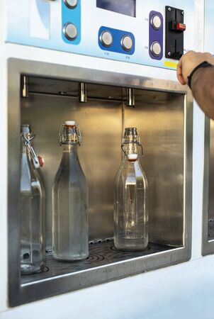 Mineral Water machine on the street. Filling mineral water bottles from a water dispenser. Pay and load drinking water. 版權商用圖片