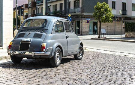 Vintage small car on traditional italian paved street. Dark grey old car.