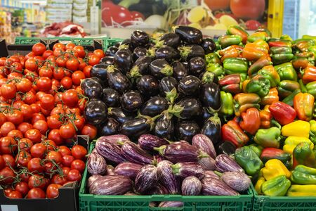 Vegetables in crates in supermarket. Arranged eggplants, peppers and tomatoes.