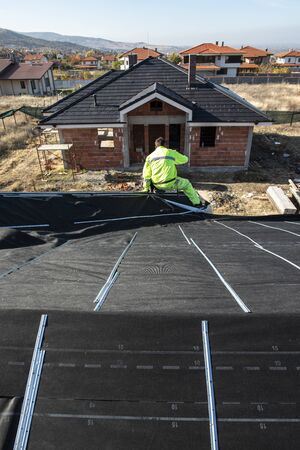 Worker on the top of the house making roof. Building a new house with black roof. Repair and build construction of roof. Conception for roofing, new home, real estate and constructions. Reklamní fotografie