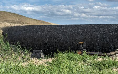 Black Oil pipeline goes out above the ground. Oil-stained pipe. Concept for oil petrol transportation with tubes. Green grass and black color oil pipe with faucet.