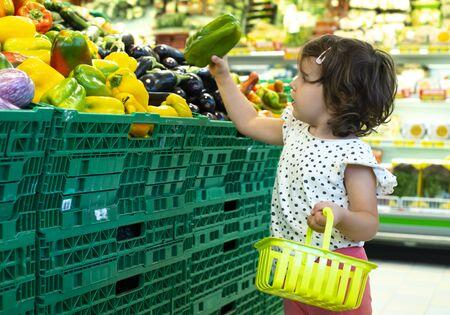 Child shopping peppers in supermarket. Concept for buying fruits and vegetables in hypermarket. Little girl hold shopping basket. Standard-Bild