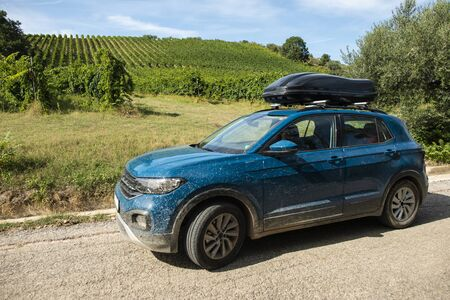 Tourist car in vineyards. Countryside and car with luggage box on top. Rural tourism concept with car and wine grapes on background. Travel concept.