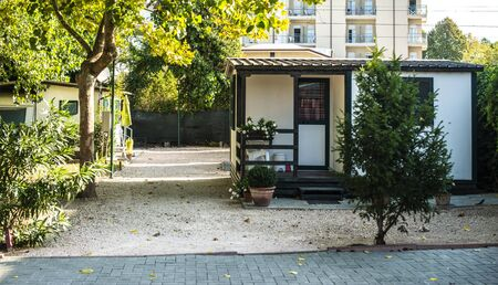 Small white bungalow on campsite. Many trees and alley on camping. Concept for rest and recreation. Travel and accommodation in the nature. Small homes.