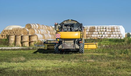 Yellow Harvester and many round bales with straw. Standard-Bild