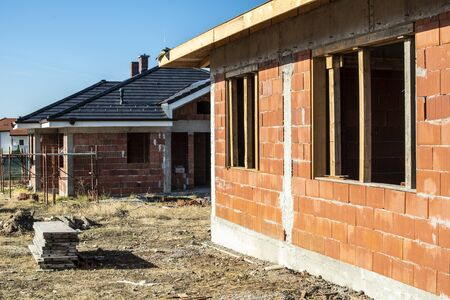 Building a new brick house with black roof. Small houses on construction site. Conception for new home, real estate and constructions.