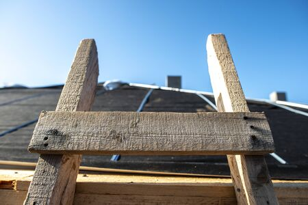 Wooden ladder on the roof of a house. Close-up wooden ladder. Sunlight. Concept of repair and construction of roof.