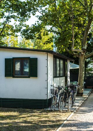 Small white bungalow on campsite. Bikes in front of bungalow. Many trees and alley on camping. Concept for rest and recreation. Travel and accommodation in the nature. Small homes.
