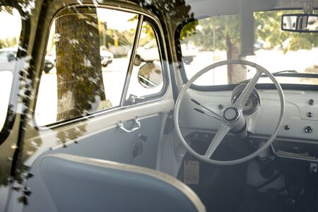 Interior of small white vintage car on the street. No people. White steering wheel. View through the window. Travel concept with car.