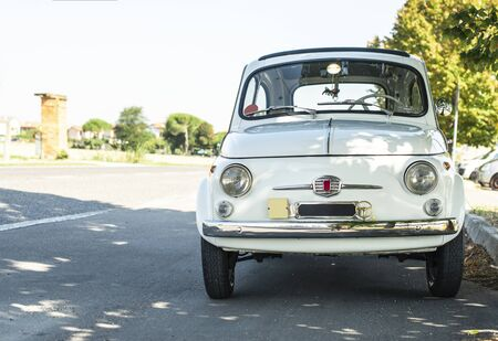 White small vintage car on the street. No people. Asphalt village road in Italy. Travel concept with car. Standard-Bild