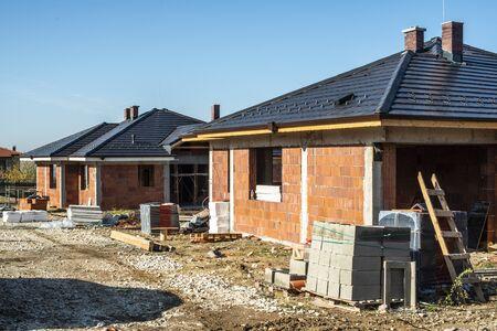 Construction d'une nouvelle maison en brique avec toit noir. Petites maisons sur chantier. Conception pour la maison neuve, l'immobilier et les constructions. Banque d'images