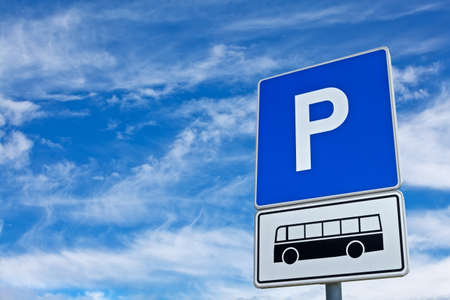 motorcoach: Blue parking sign for the bus against a blue cloudy sky