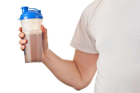 Man holding his post workout chocolate whey protein shake, ready to drink it, isolated on white