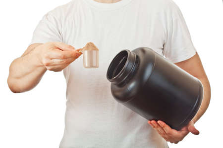 Man preparing his post workout protein shake taking a scoop of chocolate whey isolate powder from the black container, isolated on white Stock Photo
