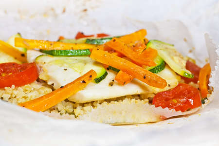 Papillote - hake fish prepared in a parchment with bulghur, tomatoes and zucchini, drizzled with olive oil photo