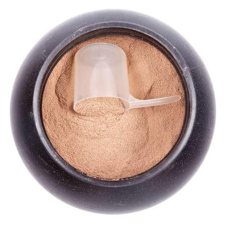 Scoop van chocolade wei-isolaat eiwit in een zwarte plastic container op wit Stockfoto