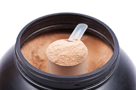 protein: Scoop of chocolate whey isolate protein in a black plastic container on white
