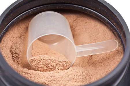Scoop of chocolate whey isolate protein in a black plastic container on white