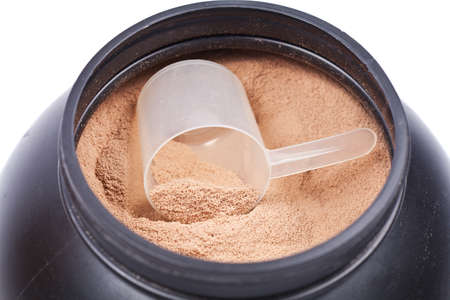 Scoop of chocolate whey isolate protein in a black plastic container on white photo