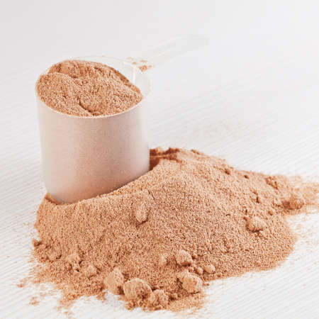Scoop of chocolate whey isolate protein powder or weight loss powder spilling out of a measuring scoop on white wooden board