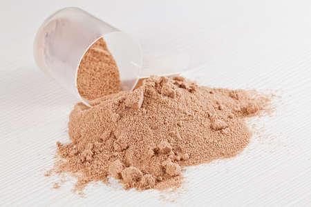 Scoop van chocolade wei-isolaat eiwit poeder of gewichtsverlies poeder morsen uit van een maatschep op wit een houten bord