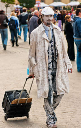 Street mime performer, dressed in white and with white makeup arriving at work in Krakow, Poland, dragging the suitcase with his equipment