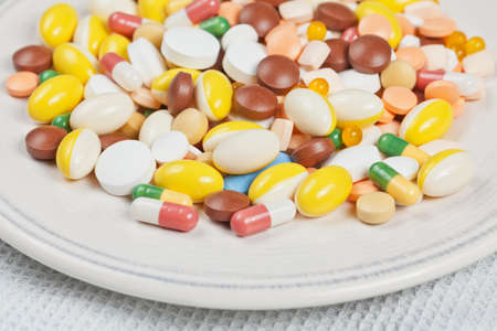 Plate filled with white, red, green, brown, blue and yellow medicine pills and capsules served as breakfast photo