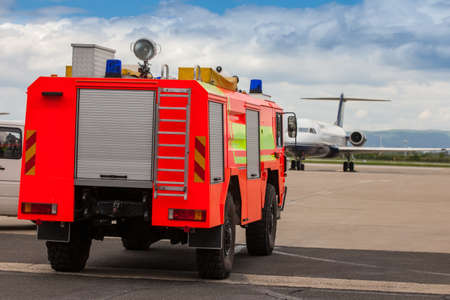 Red airport fire truck driving on the tarmac in front of the incoming airplane