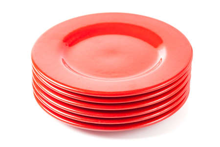 Stack of colorful red ceramics plates on white background   photo