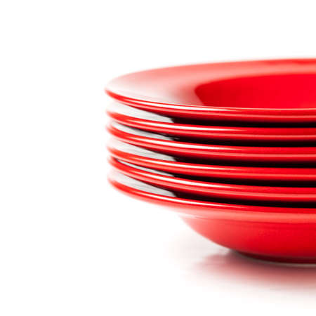 Stack of colorful red ceramics plates on white background Foto de archivo