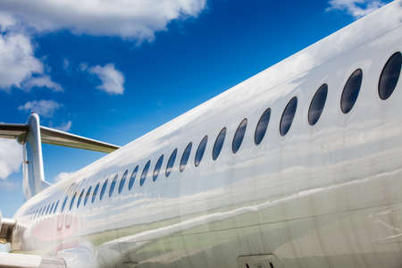 Windows and fuselage of a private airplane with tail against the cloudy sky