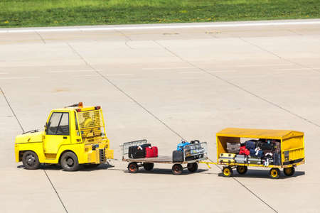 Yellow Freight trolleys with loaded baggage on the runway tarmac Reklamní fotografie