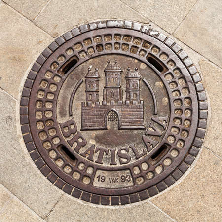 Manhole on Main Square in Bratislava, Slovakia, showing the coat of arms of the city