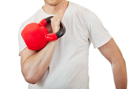 Athlete man holding the red kettlebell ready to raise it during clean and press, isolated on white background  photo