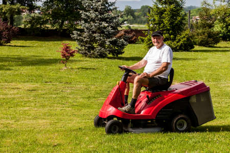 Senior man driving a red lawn mower  tractor  photo