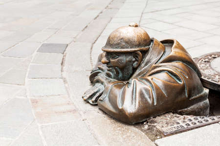 sightseeng: Cumil - statue of a man peeking out from under a manhole cover on May 9, 2013 in Bratislava, Slovakia. Popular tourist attraction was made in 1997 by sculptor Viktor Hulik. Editorial