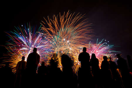 colorful light display: Big fireworks with silhouettes of people watching it Stock Photo