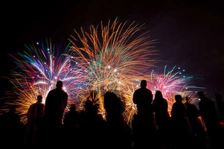Grote vuurwerk met silhouetten van mensen kijken