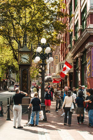 Tourists gather around Steam Clock in Gastown, Vancouver, Canada. Gastown was Vancouver