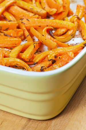 heatproof: Peeled and sliced fresh organic carrots with olive oil, garlic and thyme roasted in a ceramic tray  Stock Photo
