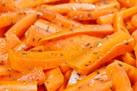 heatproof: Peeled and sliced fresh organic carrots covered in olive oil and thyme prepared to be roasted in a ceramic tray Stock Photo