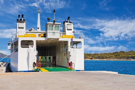 ferryboat: Car ferry boat in Adriatic Sea in Croatia with the door open in preparation of loading the cars waiting on the dock