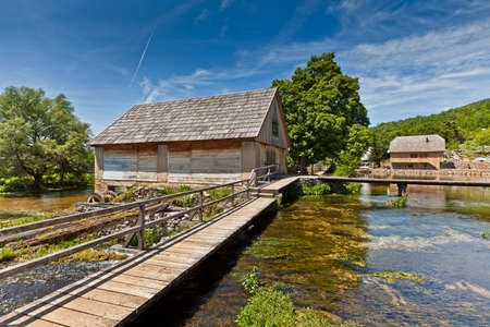 Summer scene in rural landscape - wooden mill houses above the lake in Majerovo vrilo in Sinac, Croatia, the origin of river Gacka  photo