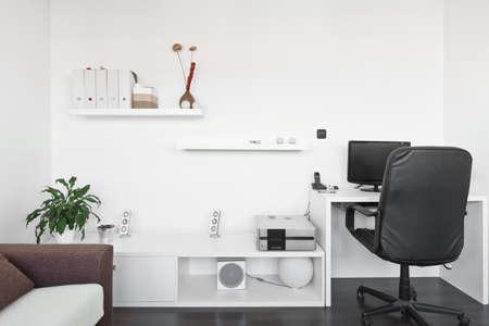 Moderne woonkamer met computer bureau en het scherm, bank en tafel met wit tapijt op donkere bruine houten vloer