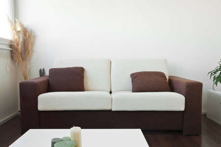 living apartment: White and brown fabric sofa in the living room with brown cushions Stock Photo