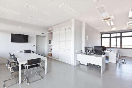 Moderne kantoor met witte meubels, kast, congresbalie en muren en een plasma-tv aan de muur Stockfoto