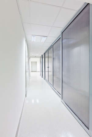 hospital corridor: Modern white long corridor with glass doors on one side