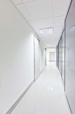 Moderne witte lange gang met glazen deuren aan een zijde